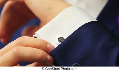 Stylish groom in blue luxury suit wearing cufflinks close up
