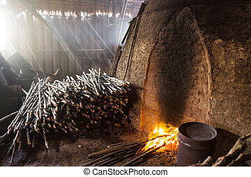 Pile of slow burning wood at charcoal factory, Thailand