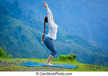 Woman doing yoga asana Utkatasana outdoors - Young sporty...