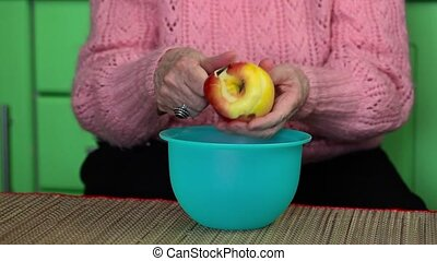 Old woman peeling an apple
