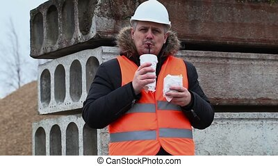 Worker with soda and french fries at construction site