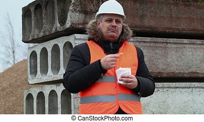 Worker eating french fries at construction site