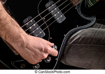 Man Playng Bass Guitar - Detail of an electric guitar. Hands...