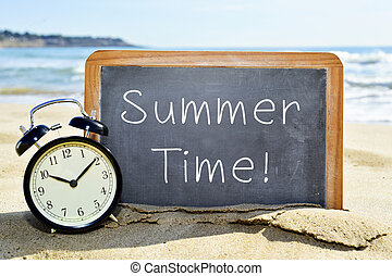 alarm clock and chalkboard with the text summer time - an...