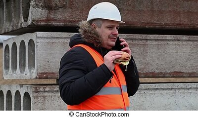 Worker with smartphone and hamburger at outdoor