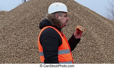Worker eating hamburger at the pile of crushed stone