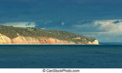 Coast In Afternoon Sun - Cove with cliffs and beach in the...