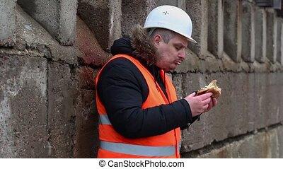 Worker eating hamburger at outdoor