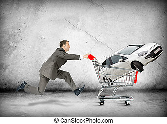 Businessman pushing shopping cart with car on grey...