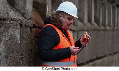 Worker with tablet PC and hamburger at outdoor