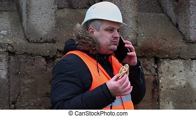 Worker with hamburger talking on smartphone at outdoor