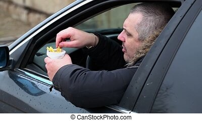 Man with french fries in the car