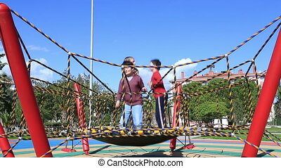 Cute kids jumping trampoline at the playground - Kids having...
