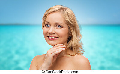 smiling middle aged woman touching face over sea - beauty,...