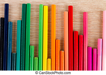 Equalizer concept - Abstract row of colorful pens on wooden...