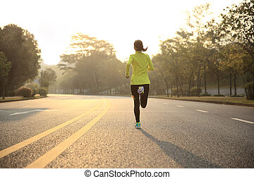 young fitness woman runner athlete running at road