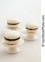 Macarons on cake stand - Three white macarons with chocolate...