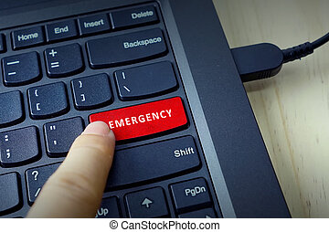 Close up of finger on keyboard button with EMERGENCY word