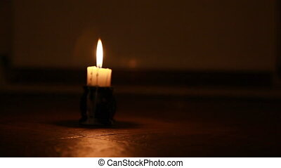 Candle in the night on stone floor