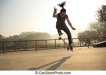 silhouette of skateboarder skateboarding at sunrise...