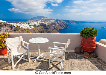 Table and chairs on roof with a panorama view on Santorini...