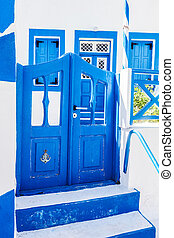 Traditional Greek stone house, blue gate and window...