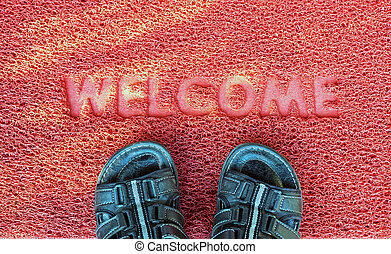 Welcome capet with foot ware on it.