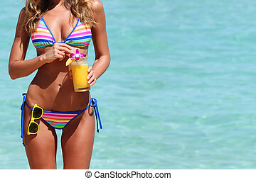 Woman with cocktail on beach - Beautiful woman in bikini...