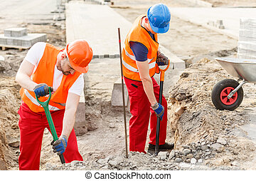 Workmen pouring sand into barrow - Picture of tough workmen...