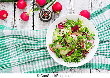 Fresh salad of cucumbers, radishes and herbs Top view