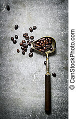 Roasted coffee beans in old spoon On the stone table