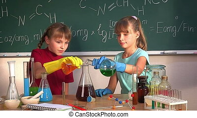 Child in chemistry class. - Children looks into flask in...