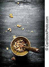 Shelled walnuts in a mortar with pestle.