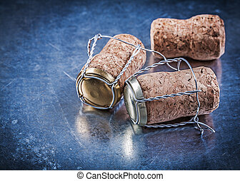 Alcohol cork plugs with twisted wires on metallic background