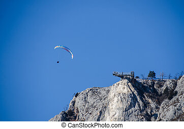 paragliders at rock wall - paragliders hovering at high rock...