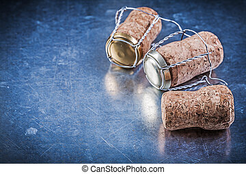 Alcohol cork stoppers with twisted wires on metallic background