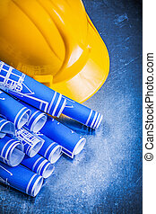 Blue rolled blueprints yellow hard hat on metallic background co