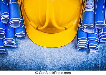 Blue rolled engineering drawings yellow building helmet on...