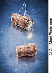 Champagne corks with twisted wires on scratched metallic backgro