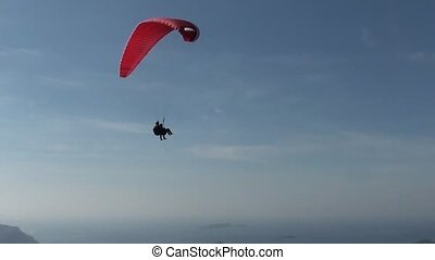 Two parachutes gliding above heads of tourists - Two...