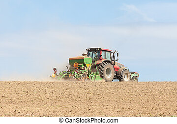 Farmer planting crops with a planter with a large hopper, skyline view