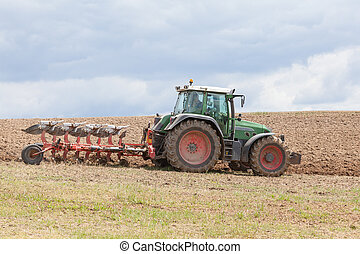 Farmer ploughing an overwintered fallow field with a tractor...