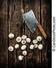 Fresh mushrooms with an old hatchet On wooden background