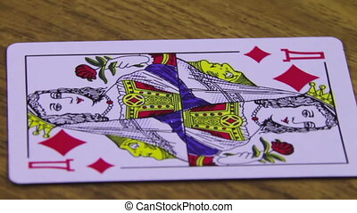 Playing Card Rotates on a Wooden Table - Playing card suits...