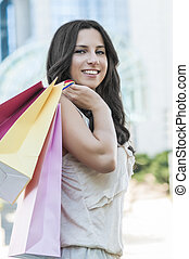 Happy Shopper - Beautiful woman with her shopping bags in...