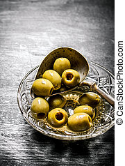 Olives in olive oil with an old spoon On black rustic...