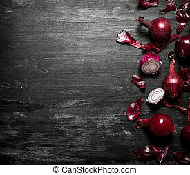 Red onion On black rustic background - Red onion On the...