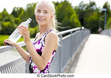 Smiling young woman having her break after working out -...