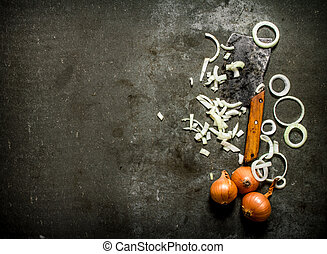 chopped onion with an old hatchet. On a stone background.