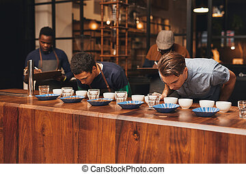 Barista training in a modern roastery with managers taking...